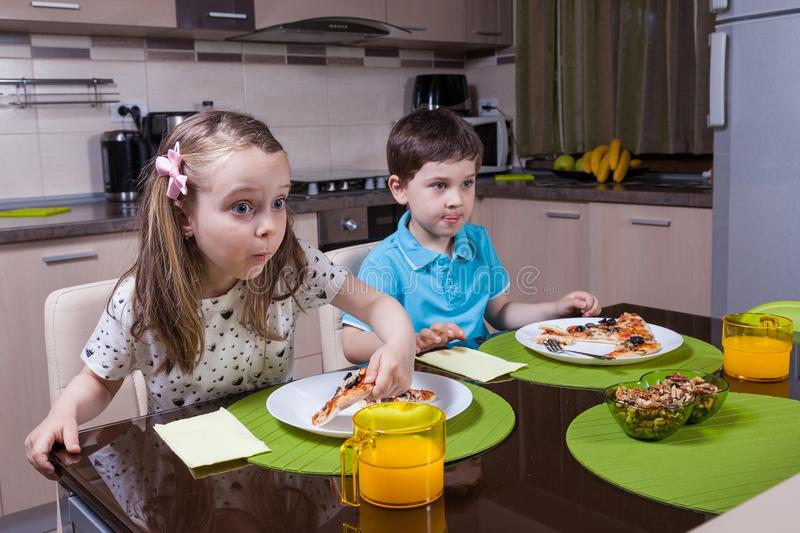 Children captivated by a TV show while eating. Pizza royalty free stock photography