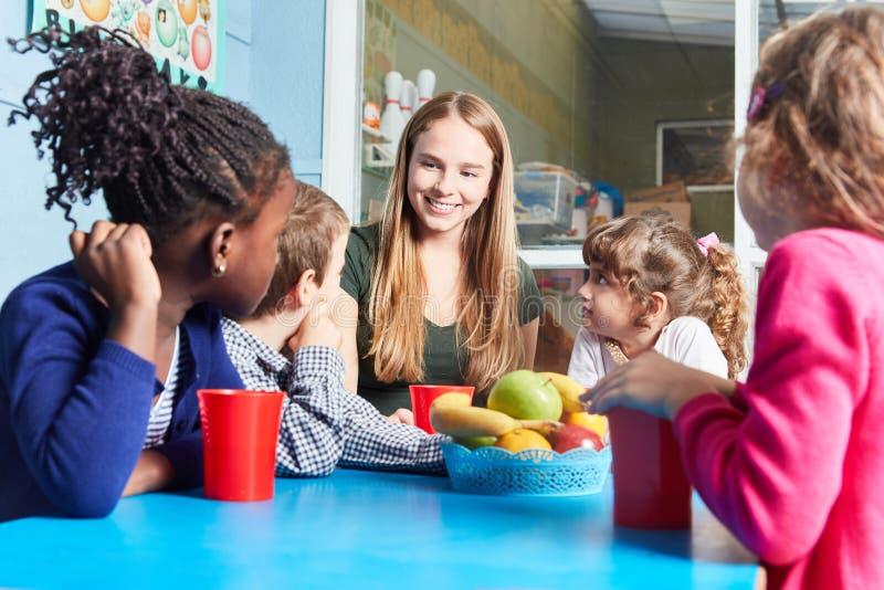 Children and caregiver eat fruit together stock photos