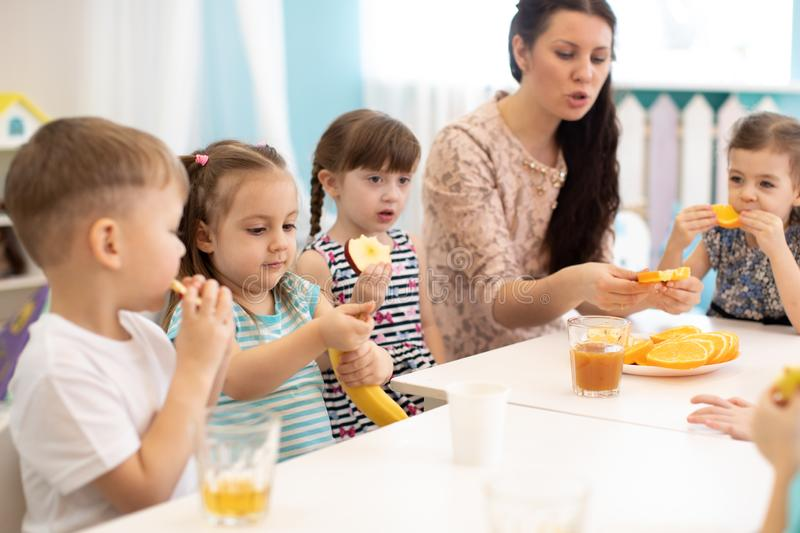 Children and carer together eat fruit as a snack in the kindergarten, daycare or school. Children and carer together eat fruit as a snack in the kindergarten royalty free stock images