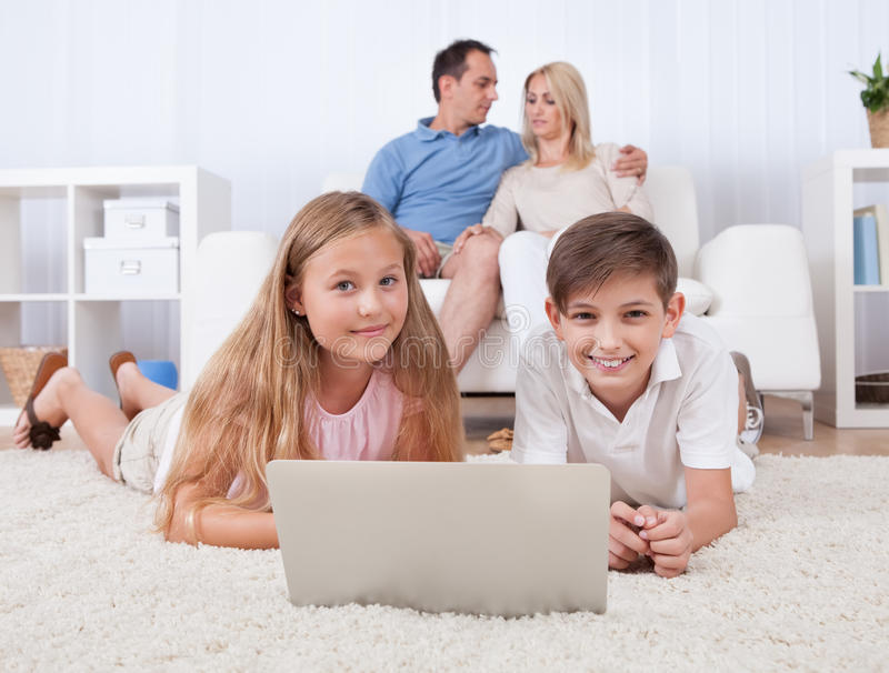 Download Children On The Carpet Using Tablet And Laptop Stock Photo - Image: 27924262
