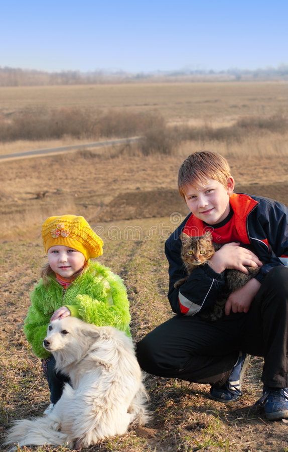 Children with cat and dog. Outdoor royalty free stock photo