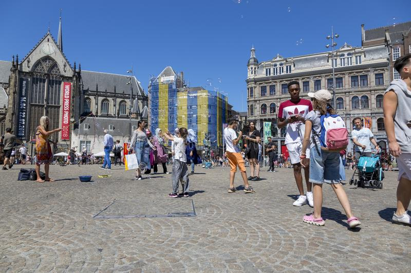 Children catch soap bubbles in the central Dam Square in Amsterdam royalty free stock photos