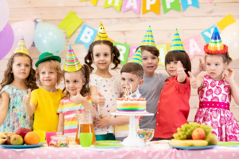 Children celebrate birthday and show thumbs up. Kids group on party. Children celebrate birthday and show thumbs up stock photo