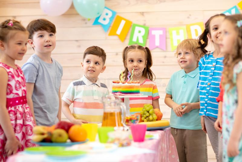 Children celebrating birthday party. Kids stand arround festive table stock image