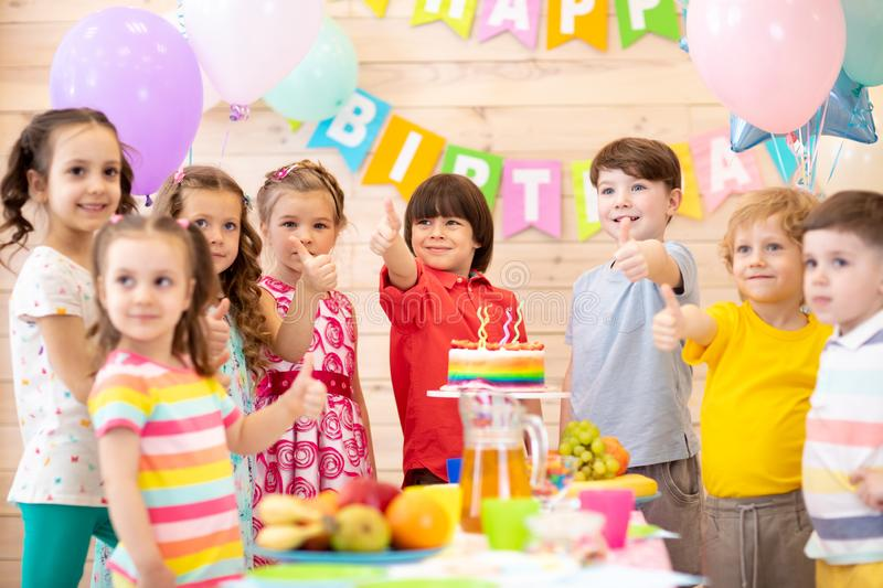 Children celebrating birthday party. Kids stand arround festive table and show thumbs up royalty free stock image