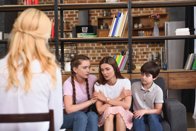 Children cheering up depressed mother on family therapy session by female. Counselor stock images
