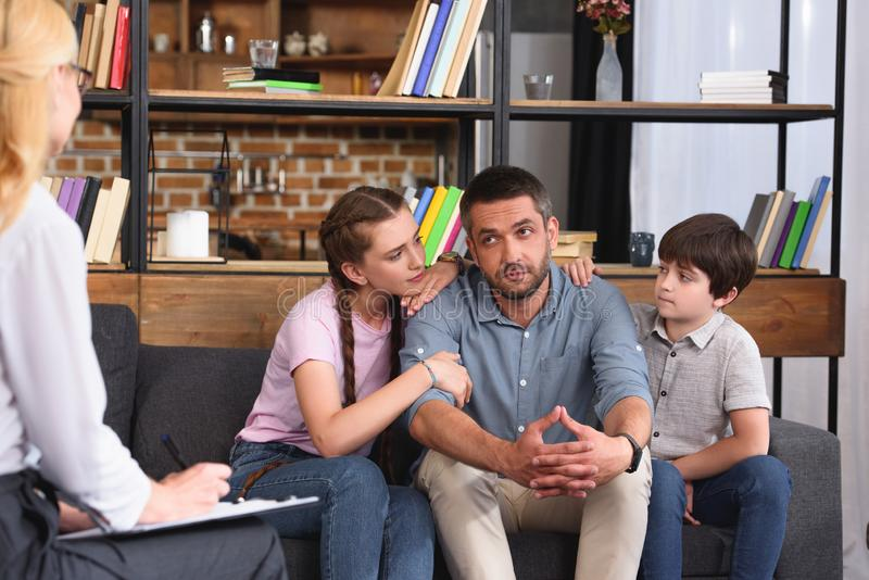 Children cheering up father while he talking to female counselor on therapy. Session royalty free stock image