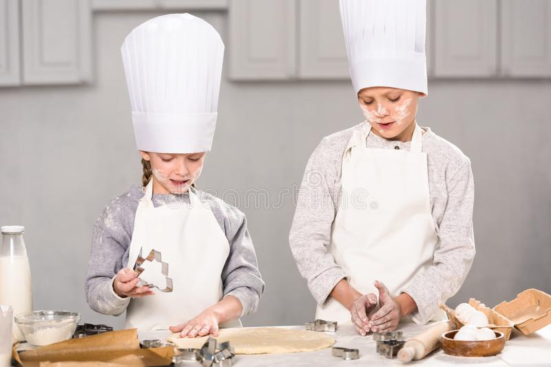 Children  in chef hats and aprons cutting out dough for cookies at table. In kitchen stock image