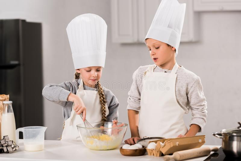 Children in chef hats and aprons whisking eggs in bowl at table. In kitchen stock image