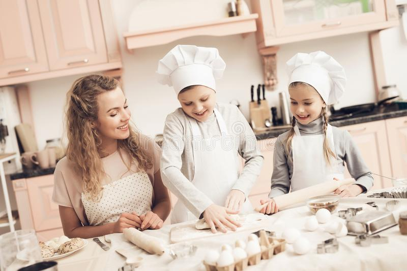 Children with mother in kitchen. Brother is kneading dough. Children in chef`s hats with mother in kitchen. Brother is kneading dough stock photos