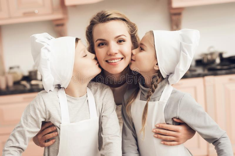 Children with mother in kitchen. Brother and sister are kissing mother on cheeks. Children in chef`s hats with mother in kitchen. Brother and sister are kissing stock photo