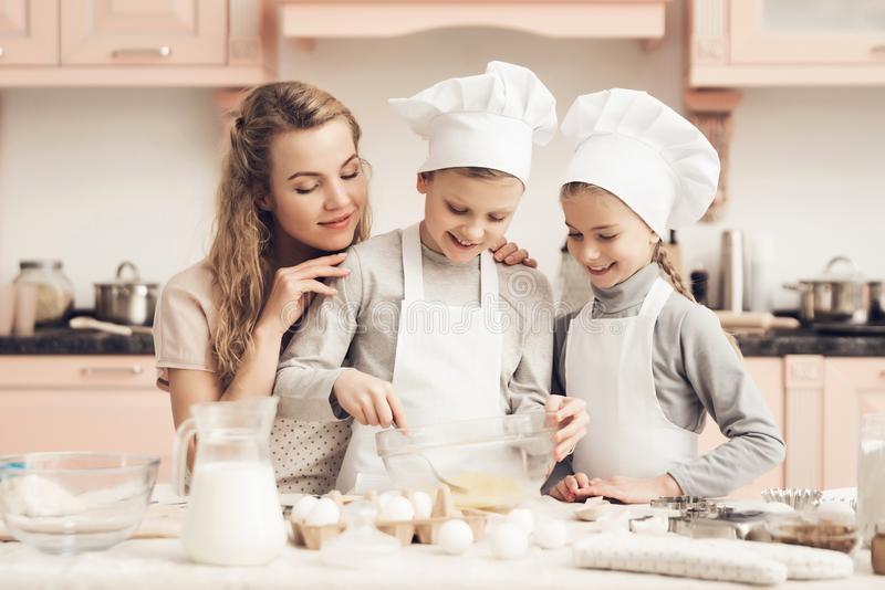 Children with mother in kitchen. Brother is whisking eggs with fork. Children in chef`s hats with mother in kitchen. Brother is whisking eggs with fork stock photo