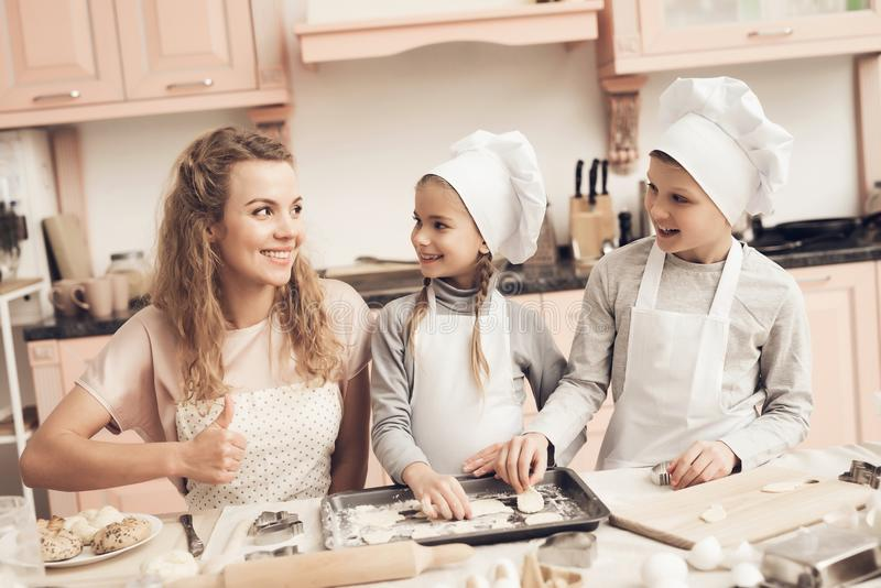 Children with mother in kitchen. Family is making cookies out of dough. Children in chef`s hats with mother in kitchen. Family is making cookies out of dough stock image