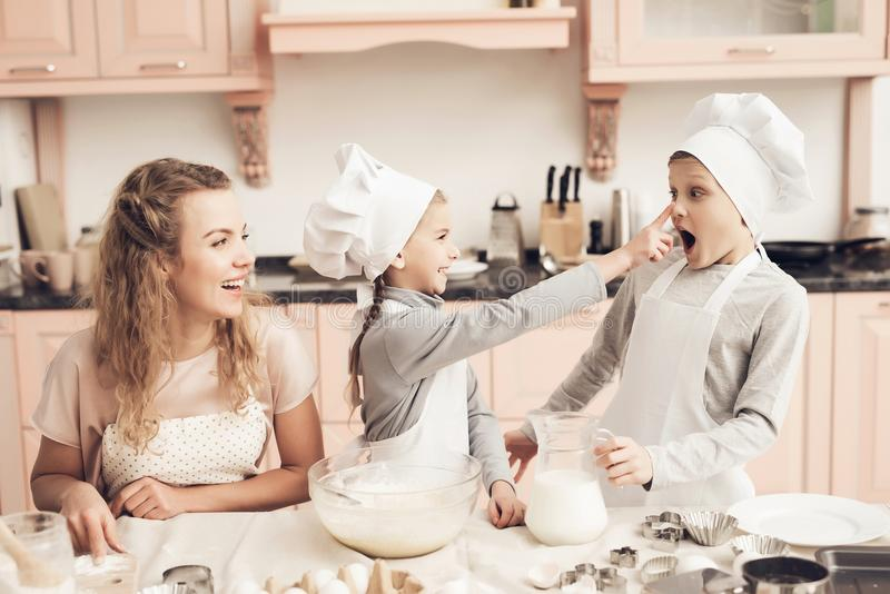 Children with mother in kitchen. Family is playfully smearing dough on nose. Children in chef`s hats with mother in kitchen. Family is playfully smearing dough royalty free stock photography