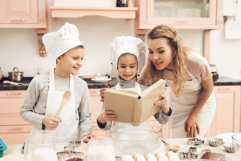Children with mother in kitchen. Family is reading recipe in cookbook. stock photos