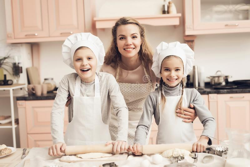 Children with mother in kitchen. Family is ready to roll out dough. Children in chef`s hats with mother in kitchen. Family is ready to roll out dough stock image