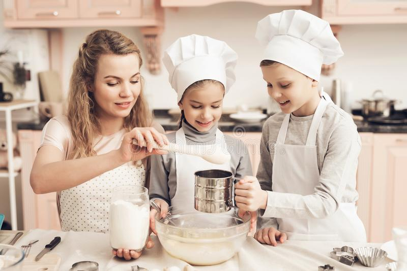 Children with mother in kitchen. Mother is adding flour, brother is sifting it. Children in chef`s hats with mother in kitchen. Mother is adding flour, brother royalty free stock photography