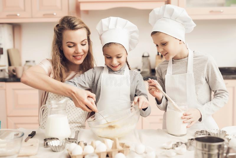Children with mother in kitchen. Mother is helping kids stir mix in bowl. stock photography