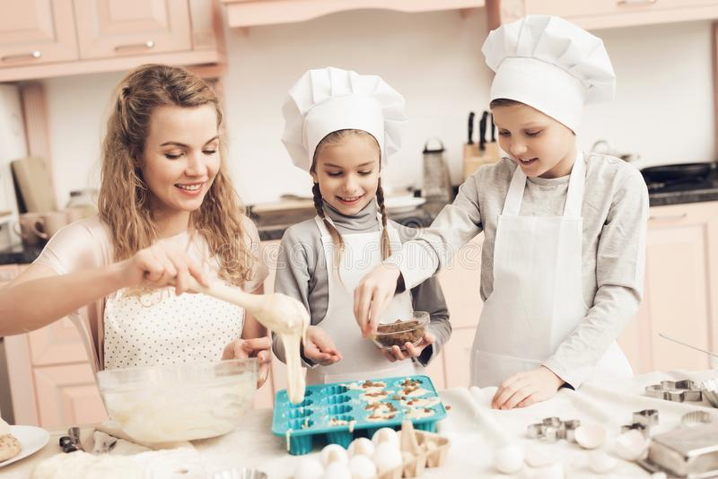Children with mother in kitchen. Mother is putting dough in baking dish and kids are adding raisins. Children in chef`s hats with mother in kitchen. Mother is stock photo