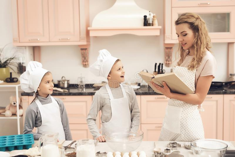 Children with mother in kitchen. Mother is reading cookbook. Children in chef`s hats with mother in kitchen. Mother is reading cookbook stock photos