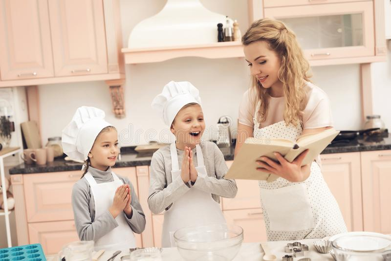 Children with mother in kitchen. Mother is reading cookbook. royalty free stock images