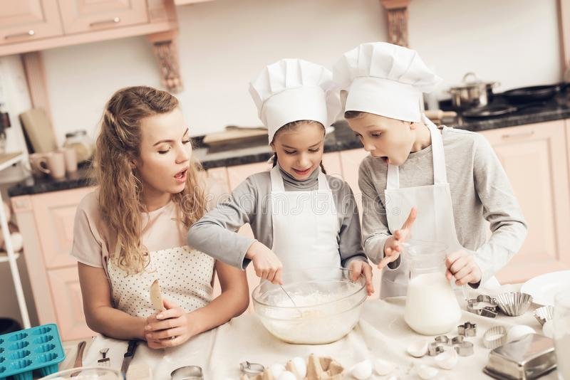 Children with mother in kitchen. Sister is stirring dough and brother is holding milk. Children in chef`s hats with mother in kitchen. Sister is stirring dough royalty free stock photos