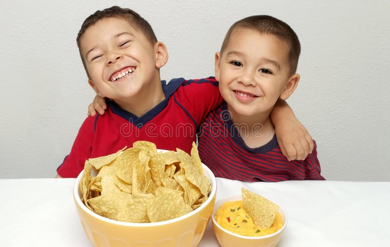 Children and chips. Two young brothers ready to enjoy a huge bowl of tortilla chips and some queso royalty free stock photos