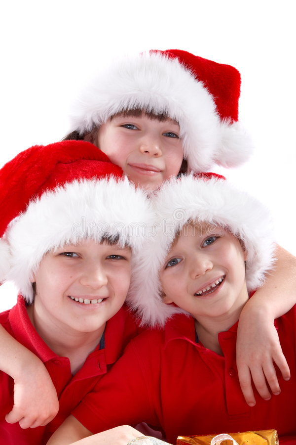 Children in Christmas hats. Three smiling children wearing christmas hats on white background royalty free stock photography