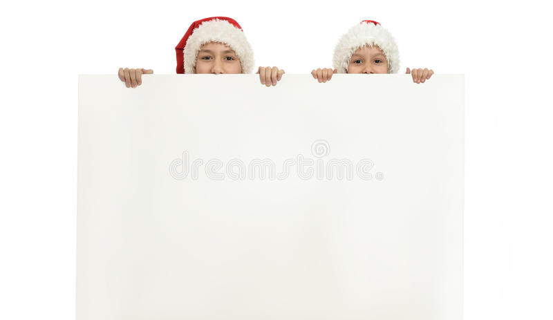Children in christmas hats. Little children in christmas hats holding white poster stock photos