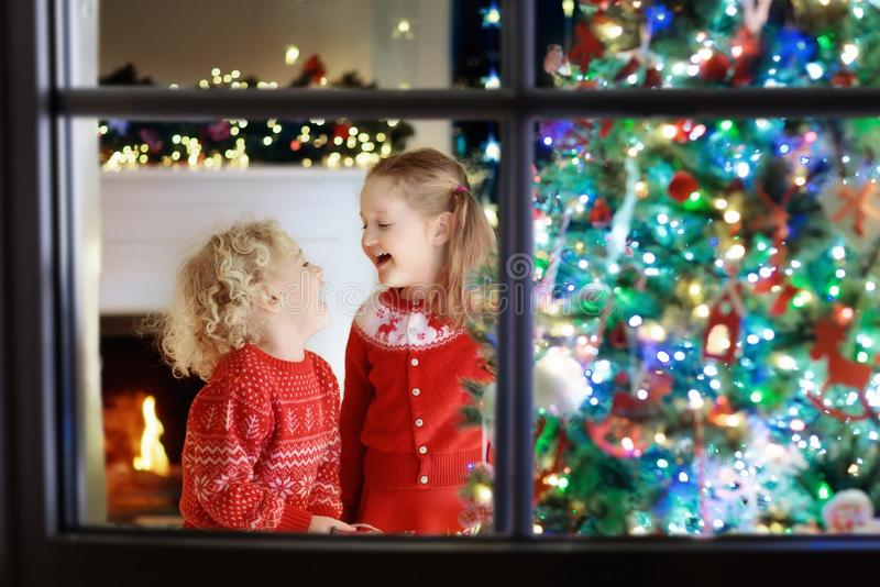 Children at Christmas tree. Kids at fireplace on Xmas eve. Children at Christmas tree and fireplace on Xmas eve. Family with kids celebrating Christmas at home stock photo