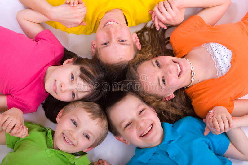 Children in a circle. Five smiling children, holding hands, laying in a circle with their heads together, caucasian/white