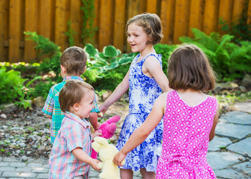Children in a Circle Playing Ring Around the Rosie. Girls and boys are holding hands together in a circle playing a game of ring around the rosie holding royalty free stock photography