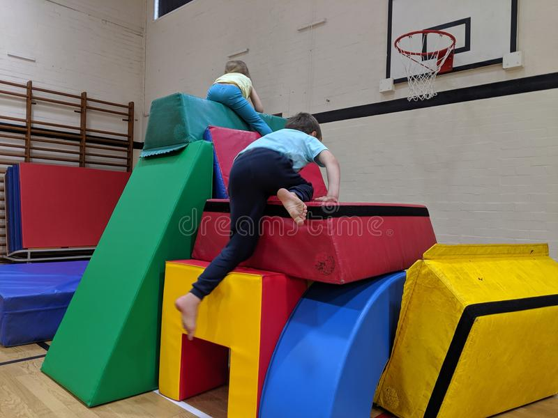 2 children climbing to the top of a soft play castle stock photography