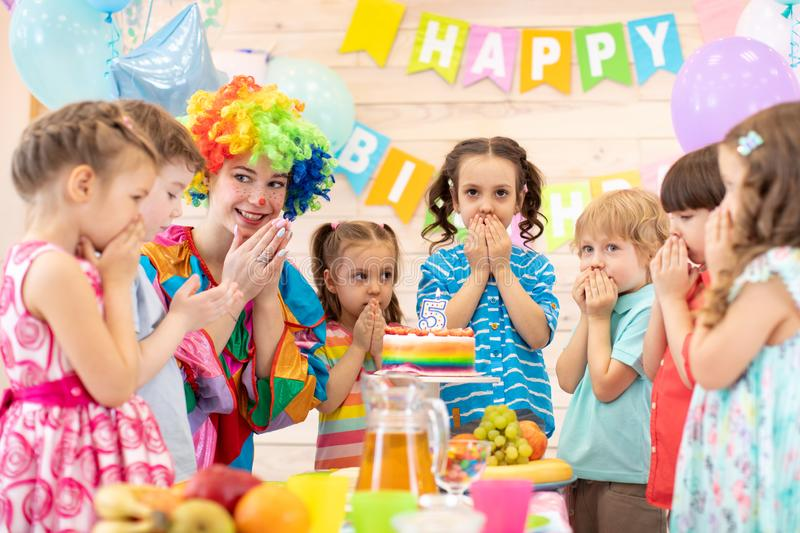 Children with clown celebrating birthday party. Kids stand arround festive table waiting surprise stock image