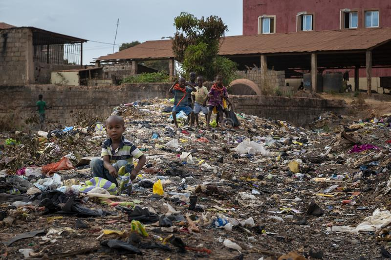 Children collecting garbage at a landfill in the city of Bissau, in Guinea-Bissau. Bissau, Republic of Guinea-Bissau - February 8, 2018: Children collecting royalty free stock photography