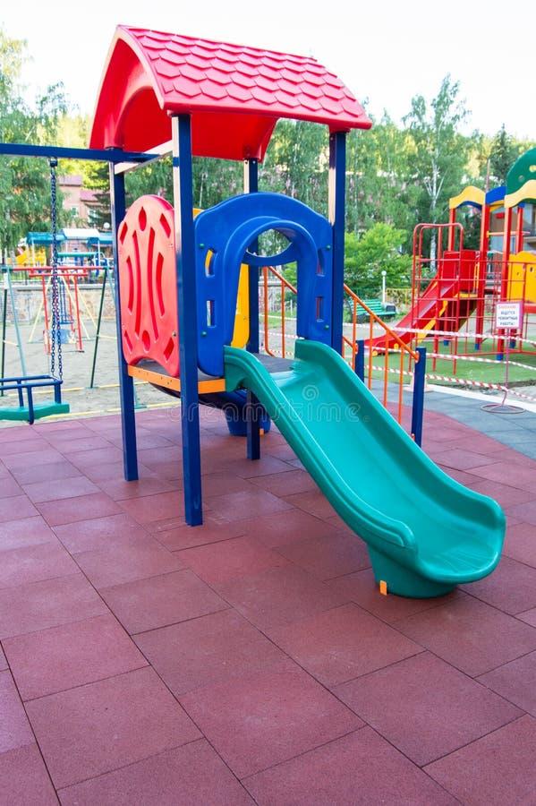 Children' coloré ; terrain de jeu de s avec des glissières et des oscillations dehors en parc en été image libre de droits