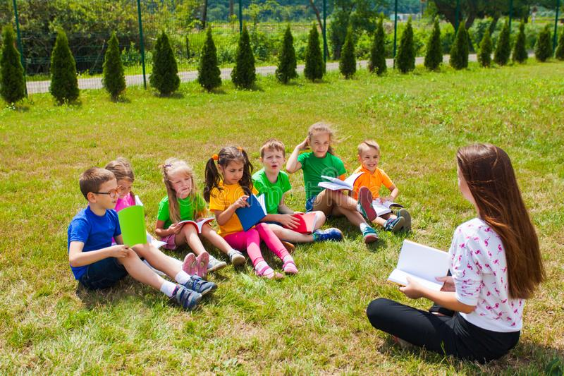 Acquaintance of the teacher and children outdoors. Children in colored clothes, along with a teacher in the park, read books stock photos