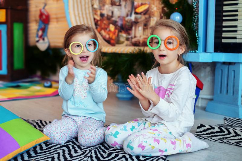 Children colored glasses to sing a song. Two sisters. The concept of Christmas and New Year. royalty free stock image