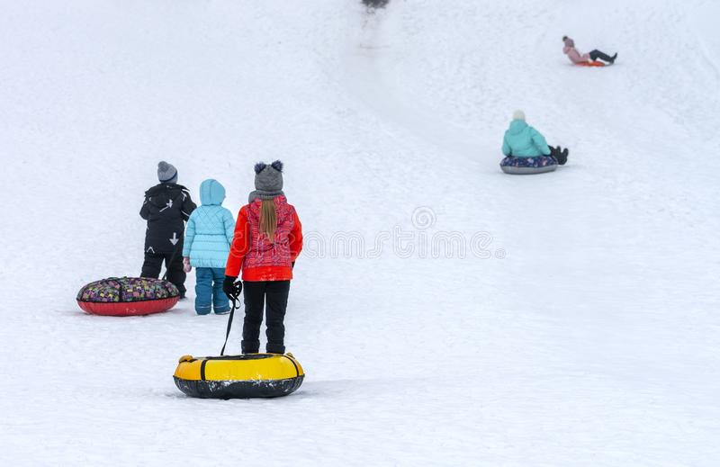 Children in colorful garments slide down the slide on inflatable rings stock photography
