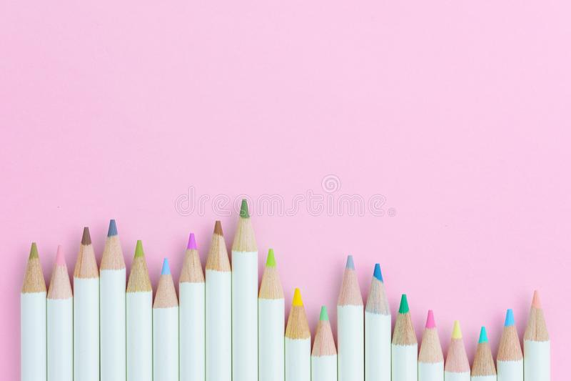 Children coloring equipment, pastel color pencils on pink paper. Background with copy space using as art or education concept stock images