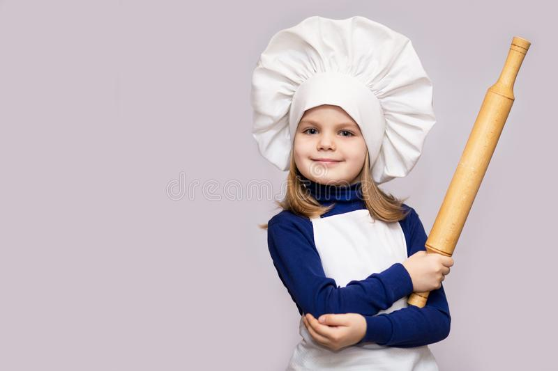 Children cook. Happy little girl in chef uniform holds rolling pin on white background. Kid chef royalty free stock photography