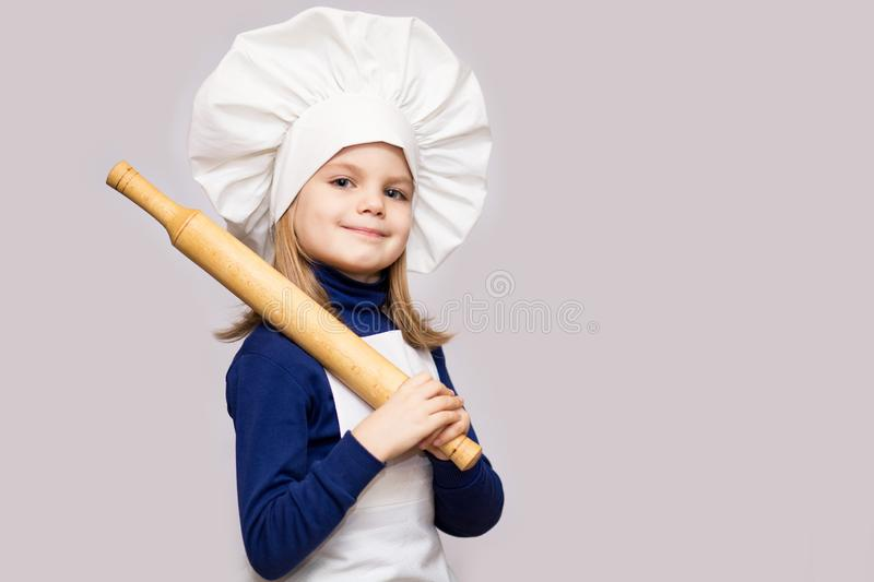 Children cook. Happy little girl in chef uniform holds rolling pin on white background. Kid chef royalty free stock images