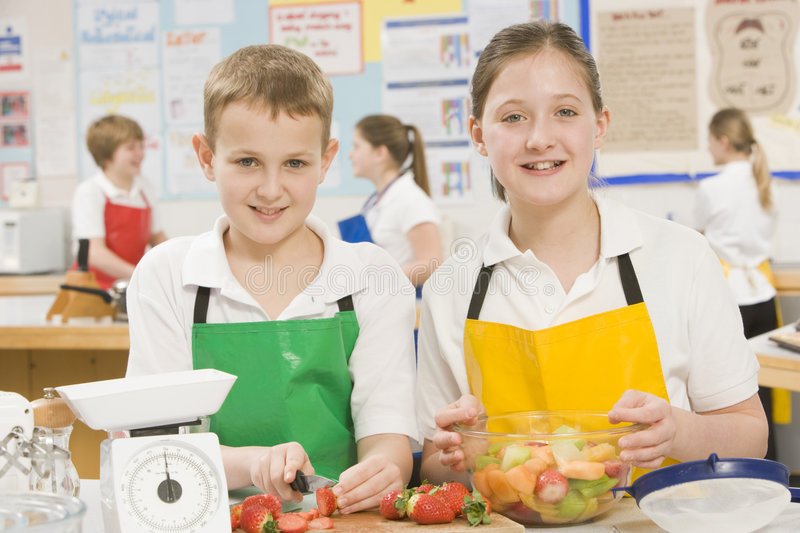 Children in cooking class. Schoolchildren at school in a cooking class smiling royalty free stock photo