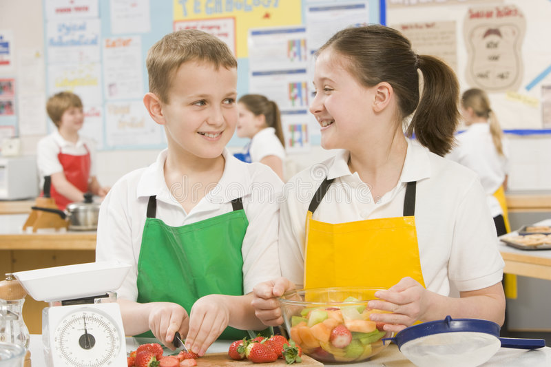 Children in a cooking class. Schoolchildren at school in a cooking class smiling royalty free stock photography