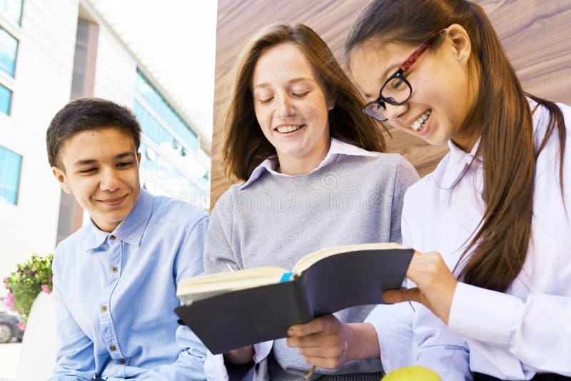 Children Copying Homework by School Building stock images