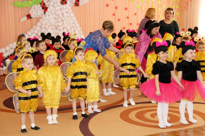 Children in costumes of bees and Mickey Mouse in matinee at kindergarten stock photo