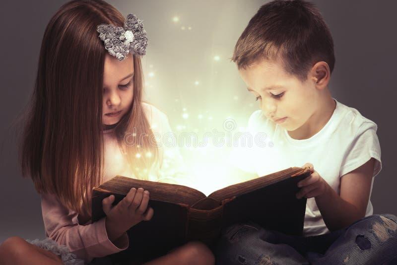 Children couple opened a magic book. Small couple opened a magic book royalty free stock photography