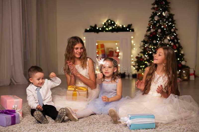 Children cover gifts at the Christmas tree lights garlands new year stock photography