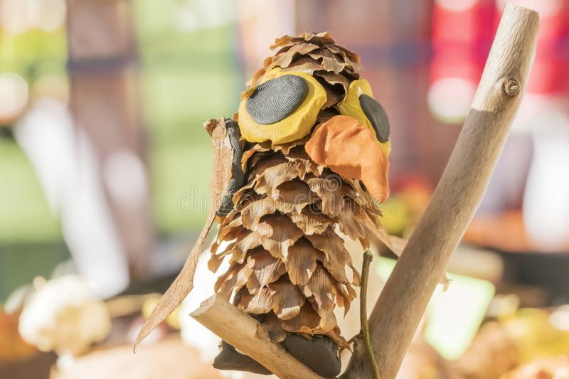 Children crafts - bird made from cones. Children crafts - a bird with a large beak, made of cones and clay, close-up stock photo