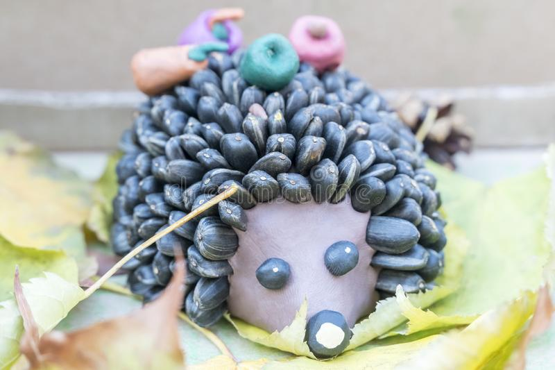 Children crafts - hedgehog from clay and seeds stock photo